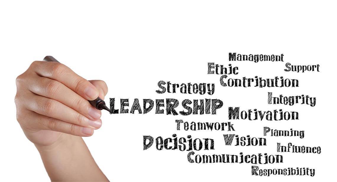 A hand writing words like leadership and strategy.