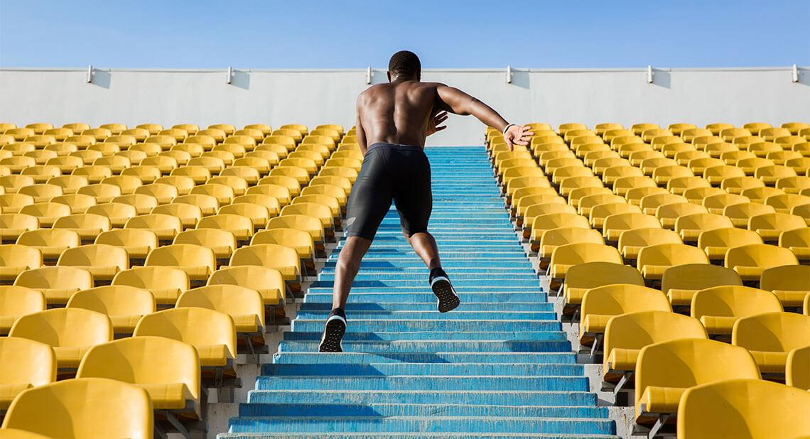 A really fit guy running up stairs at a stadium