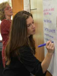 Charmaine Farber writes on a poster